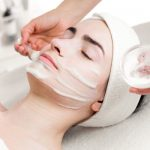 Young woman facial peeling mask applying in beauty parlour
